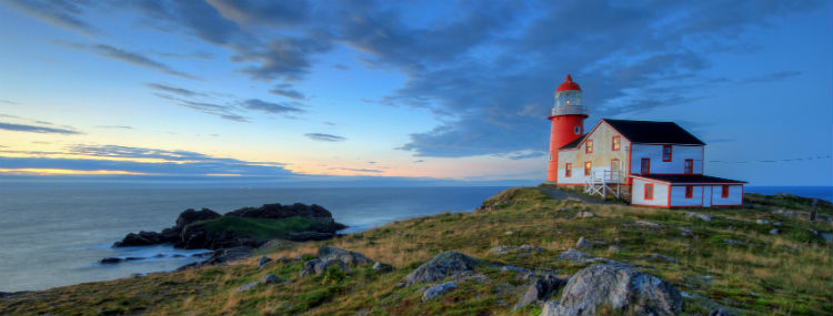 A red lighthouse perched on a rugged cliff overlooking ocean. The sky is at twilight.