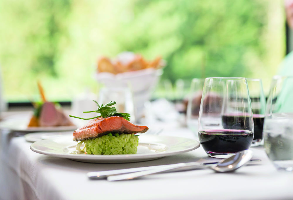 A table covered with a white table cloth. The plate in the background shows a salmon dish, and the other dishes are out of focus. there is red wine on the table.