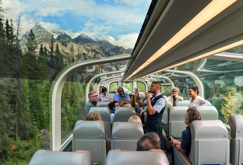 A male Rocky Mountaineer host looking out onto the landscape while holding a microphone, while guests look at him and the landscape