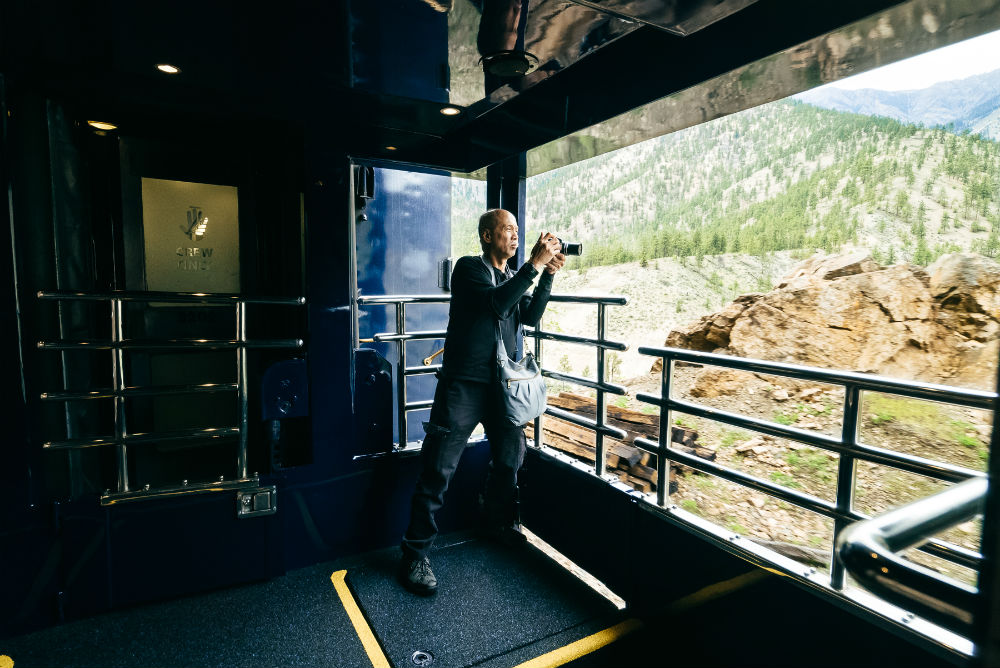 A man taking photos of the landscape from the viewing platform of the rocky Mountaineer.