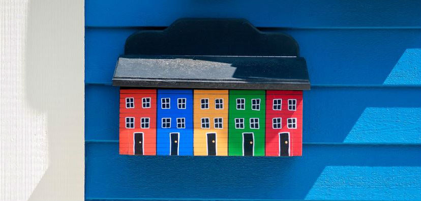 A wall sculpture of colourful St John's houses, hung up on a blue wooden wall.