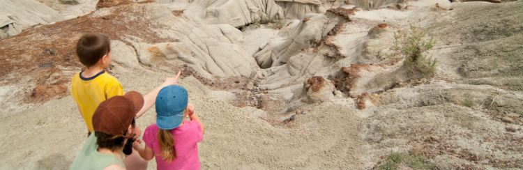 A father and his two kids looking over the Canadian Badlands landscape